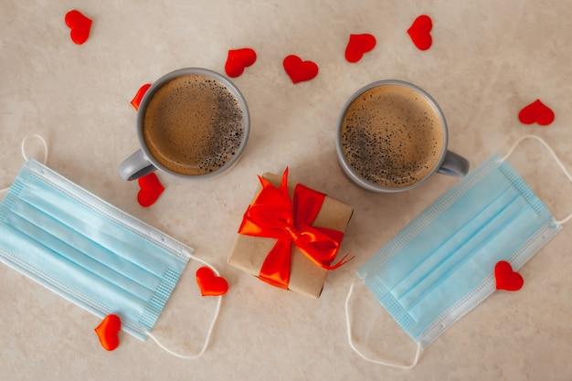 Due tazze di caffè sul tavolo, accanto a una confezione regalo con un fiocco rosso, maschere mediche e cuori di coriandoli rossi sparsi. san valentino in una pandemia.