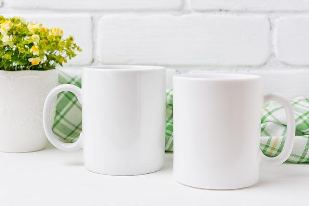 Un modello di due tazze da caffè con fiori gialli e verdi