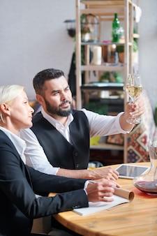 Due colleghi che si consultano sulle caratteristiche di uno dei campioni di vino mentre lavorano nella cantina del ristorante