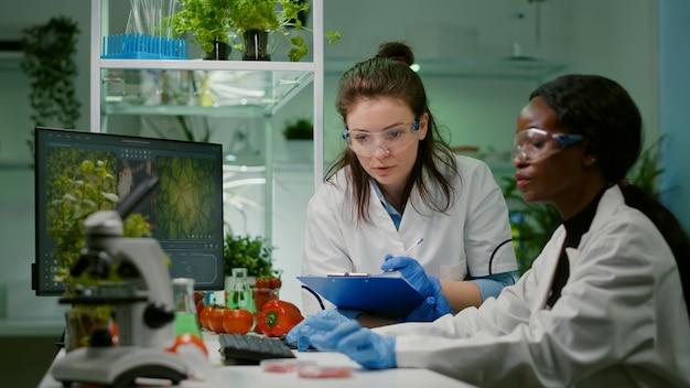 Due colleghi che controllano un campione di carne vegana che scrivono competenze biotecnologiche