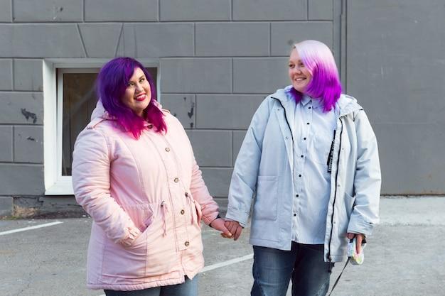 Lesbica di due colori che si tiene per mano e sorride felice coppia omosessuale all'aperto