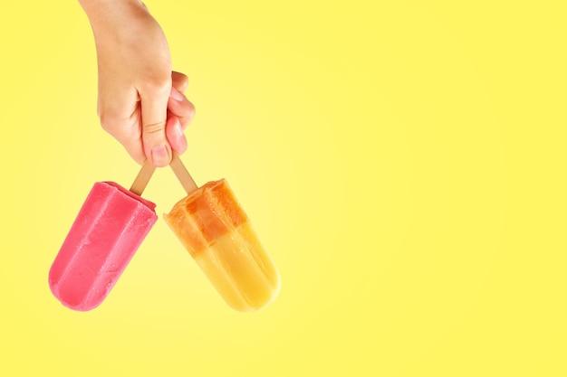 Due ghiaccioli di colore nelle mani della donna su sfondo giallo