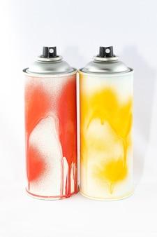 Due barattoli di vernice spray colorata su sfondo bianco