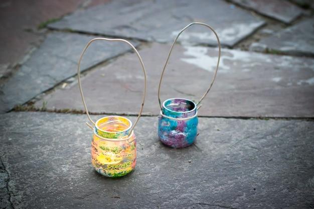 Due barattoli di vetro colorati con lampade a candela con manico in filo metallico su piastrelle da esterno in pietra, attività per bambini e concetto di idea artigianale