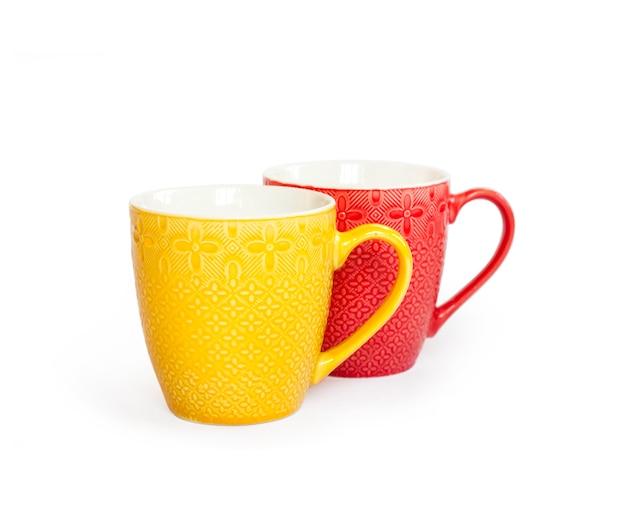 Due tazze colorate isolate su una superficie bianca con tracciato di ritaglio