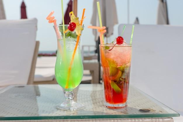 Due colorati cocktail tropicali su ghiaccio in piedi fianco a fianco su un tavolo tra sedie a sdraio e ombrelloni in una località balneare in una vacanza estiva