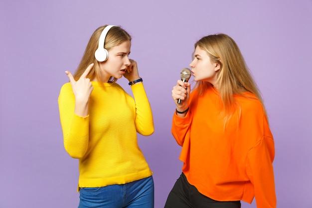 Due sorelle gemelle bionde interessate in abiti vivaci ascoltano musica con le cuffie cantano una canzone nel microfono isolato sulla parete blu viola. concetto di stile di vita familiare di persone.