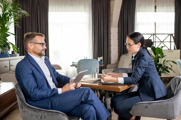 Due colleghi fiduciosi in abiti da cerimonia che discutono di momenti di lavoro e prendono decisioni durante una riunione al ristorante