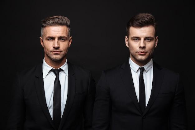 Due uomini d'affari belli fiduciosi che indossano un abito in piedi isolato su un muro nero, guardando la telecamera