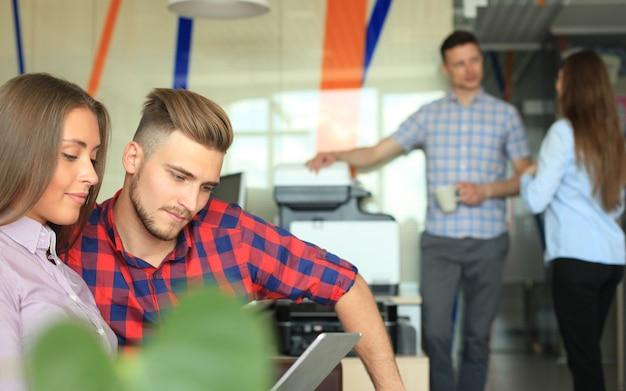 Due giovani fiduciosi che guardano il touchpad mentre i loro colleghi lavorano in background