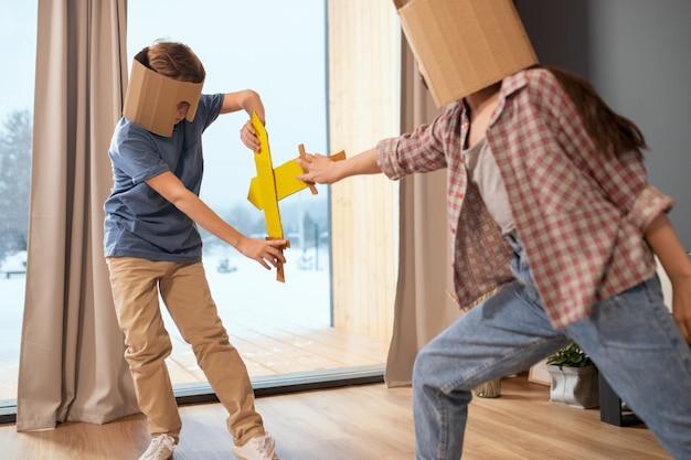 Due bambini contemporanei con elmetti di cartone che combattono con spade giocattolo contro una grande finestra con tende beige nel soggiorno