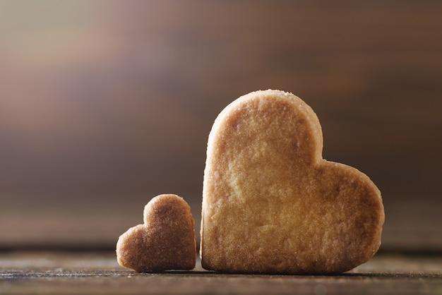 Due cuori di biscotti su fondo in legno per il giorno di san valentino