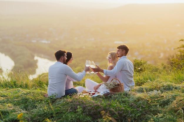 Due coppie che bevono vino a un picnic in un campo