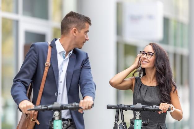 Due colleghi che usano scooter elettrici chiacchierano davanti a un edificio per uffici.