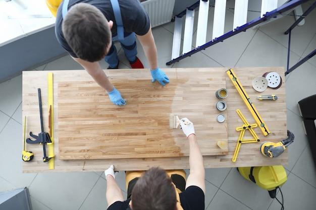 Due artigiani stanno coprendo il tavolo di legno con vernice protettiva