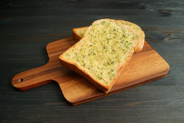Due fette biscottate croccanti e saporite fatte in casa con burro all'aglio su breadboard di legno