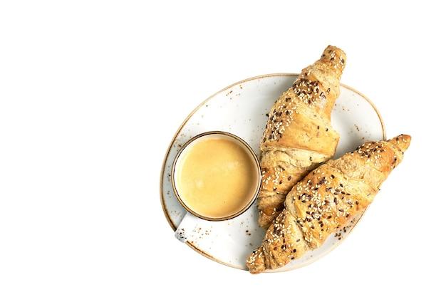 Due croissant e tazza di caffè isolati su sfondo bianco. vista dall'alto, copia dello spazio