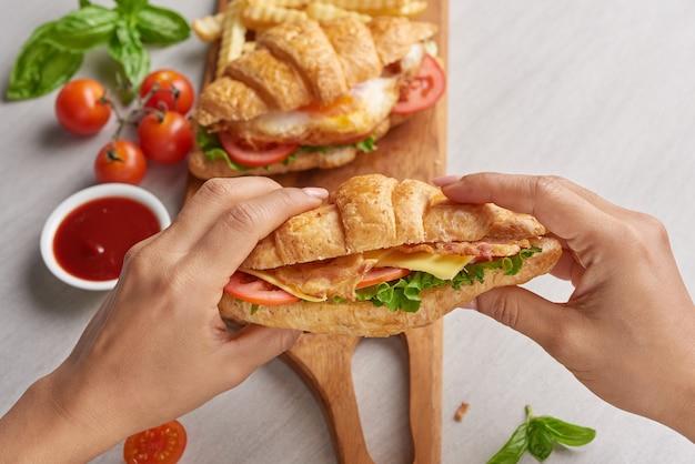 Due panini croissant sul tavolo di legno, vista dall'alto, panino con pancetta, uovo fritto. prosciutto, formaggio, pancetta, uovo fritto, pomodoro, patatine fritte e lattuga serviti nelle mani.