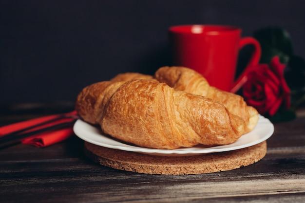 Due croissant su un piatto una tazza di caffè tavolo in legno dessert pasto. foto di alta qualità