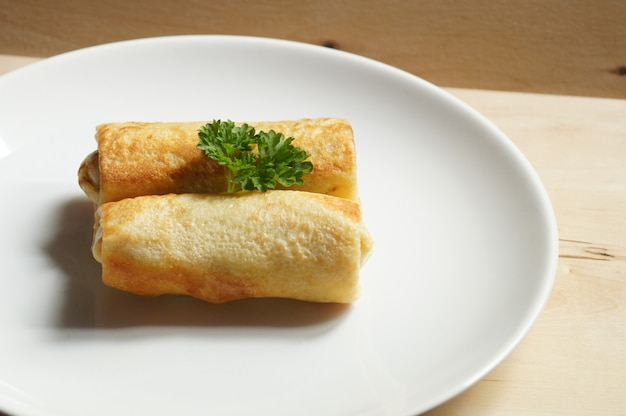 Due crocchette sul piatto bianco, tavolo in legno