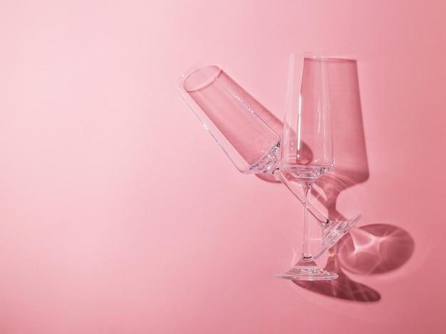Due bicchieri di cristallo su gambe lunghe su sfondo rosa. vetreria in condizioni di luce intensa.