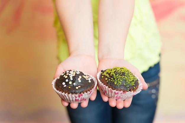 Due cupcakes di cioccolato in mano del bambino su sfondo sfocato colorato. confetteria, dessert, pasticcini, cibo, concetto di dieta malsana.