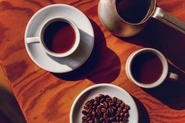 Due tazze di caffè nero e cezve sul tavolo.