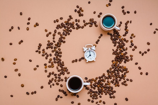 Due tazze di caffè nero in un cerchio di chicchi di caffè e una sveglia bianca su fondo beige. è ora di bere il concetto di caffè. vista dall'alto
