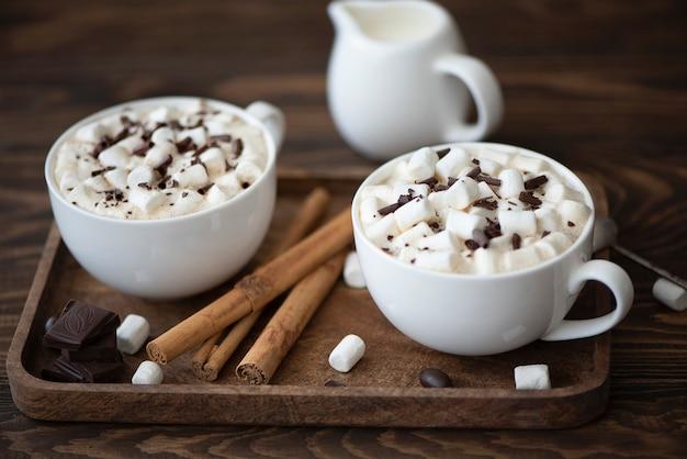 Due tazze di caffè nero con cioccolato e marshmallow