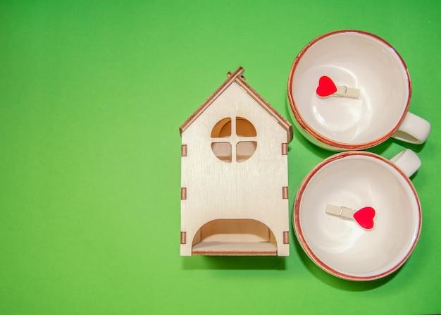 Due tazze in blu e rosa, legate con una corda, mollette rosse con cuori e una casa di legno.