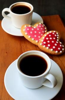 Due tazze di caffè e biscotti di glassa reale a forma di cuore punteggiato con messa a fuoco selettiva