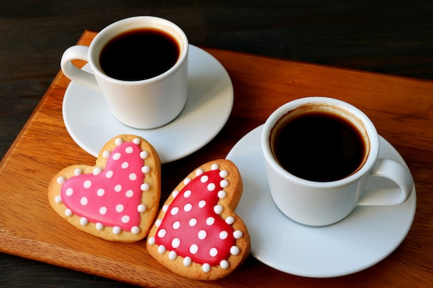 Due tazze di caffè e biscotti di glassa reale a forma di cuore punteggiato su un tagliere di legno
