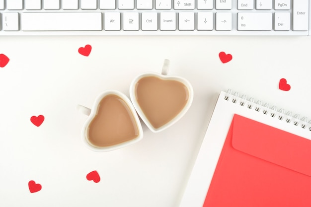 Due tazze di caffè sotto forma di cuori sul desktop dell'ufficio. concetto festivo di san valentino. vista dall'alto. lay piatto.