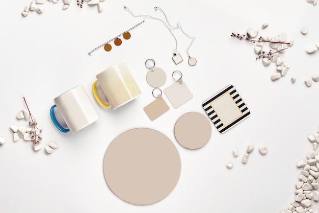 Due tazze, portachiavi di diverse dimensioni, medaglioni, supporti, bracciale, ramoscelli secchi e pietre di mare
