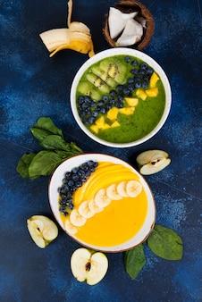 Due tazze di frullato diverso ciotola di frutti verdi e gialli. il concetto di alimentazione sana. foto verticale. vista dall'alto.