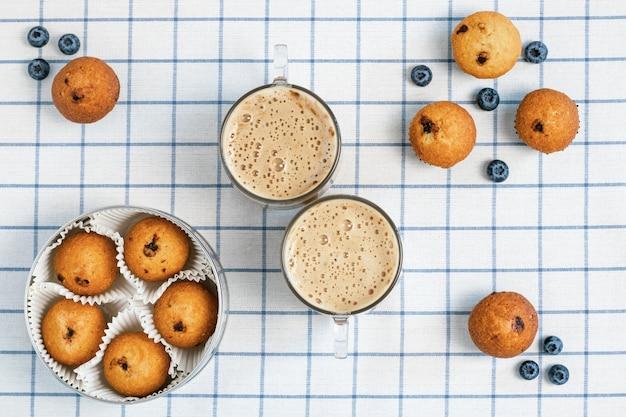 Due tazze di caffè schiumoso e muffin ai mirtilli su una tovaglia a quadretti.