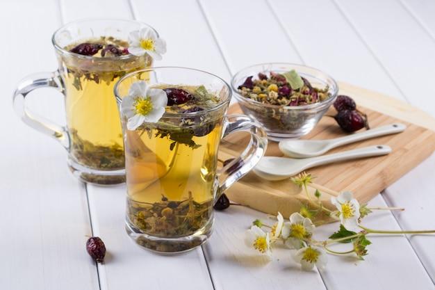 Due tazze di tisana con cinorrodo, camomilla, erbe sul tavolo di legno bianco