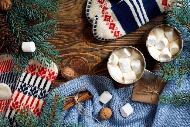 Due tazze di cioccolata calda o cioccolata con guanti marshmallow decorazioni natalizie e abete su legno...