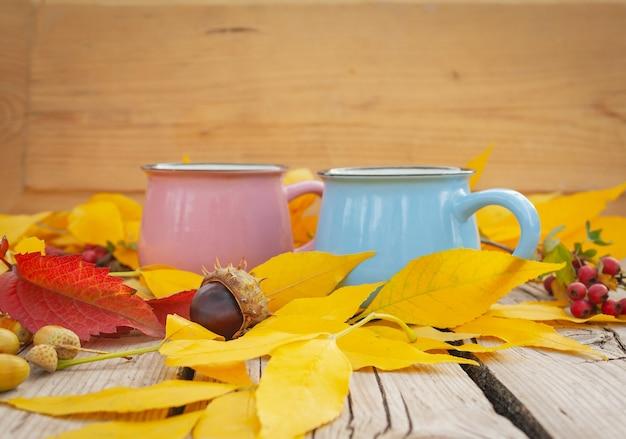 Due tazze sul tavolo con foglie autunnali gialle in giardino