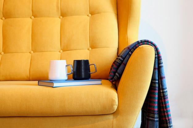 Due tazze di tè e un libro blu su un pullman giallo con una coperta dettagli di natura morta nell'interno della casa