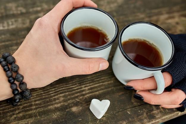Due tazze di tè in natura nelle mani delle coppie in guanti neri su una superficie di legno