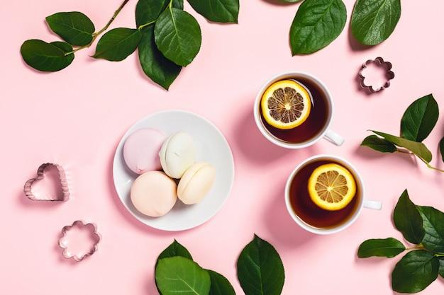 Due tazze di tè con marshmallow e rose.