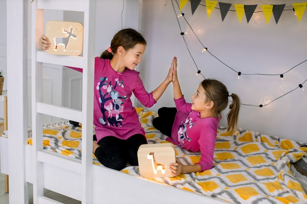 Due simpatiche sorelle di 10 anni in pigiama luminoso che scherzano, giocano e si divertono in un elegante letto a castello, tenendo in mano lampade da notte in legno e si danno il cinque a vicenda.