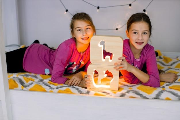 Due simpatici bambini caucasici, graziose sorelline, indossano camicie rosa, sdraiati su un letto a castello per bambini luminosi e giocano con eleganti lampade da notte in legno con immagini ritagliate.