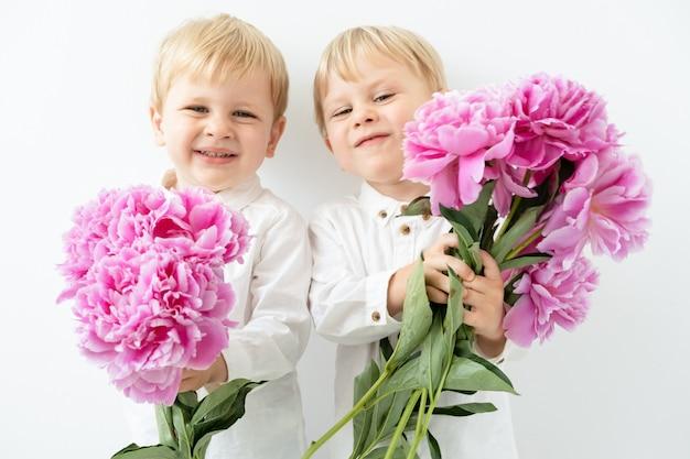 Due ragazzi gemelli biondi bambino carino con grande mazzo di peonie rosa sorridente su sfondo bianco.