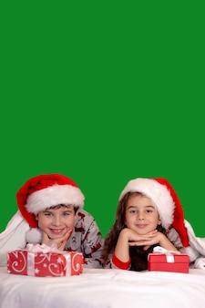 Due simpatici bambini, una ragazza e un ragazzo, in pigiama e cappelli di babbo natale, si coccolano sul letto con i regali in mano. isolato su uno sfondo verde.