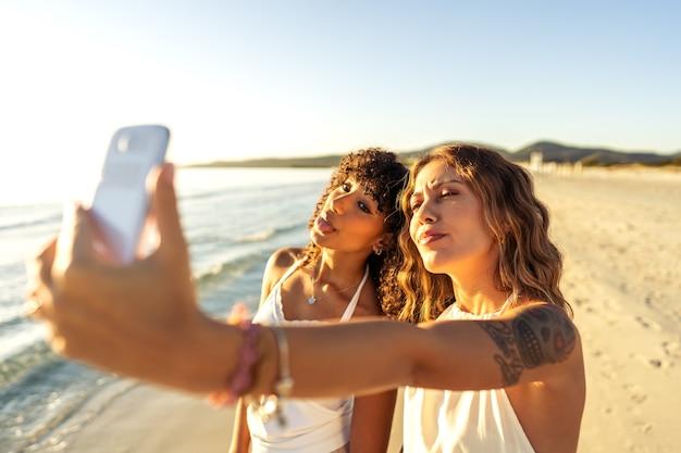 Due ragazze carine in abito bianco boho durante le vacanze estive usando lo smartphone facendo un selfie facendo facce