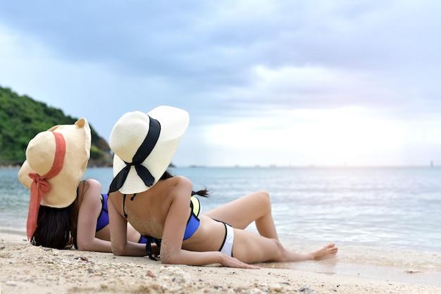 Un amico sveglio di due ragazze si distende sulla spiaggia.