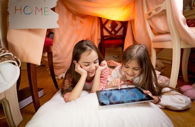 Due ragazze carine sdraiate sul pavimento in camera da letto e giocano su un tablet digitale