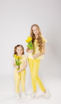 Due ragazze carine con i capelli biondi con tulipani gialli in abiti gialli